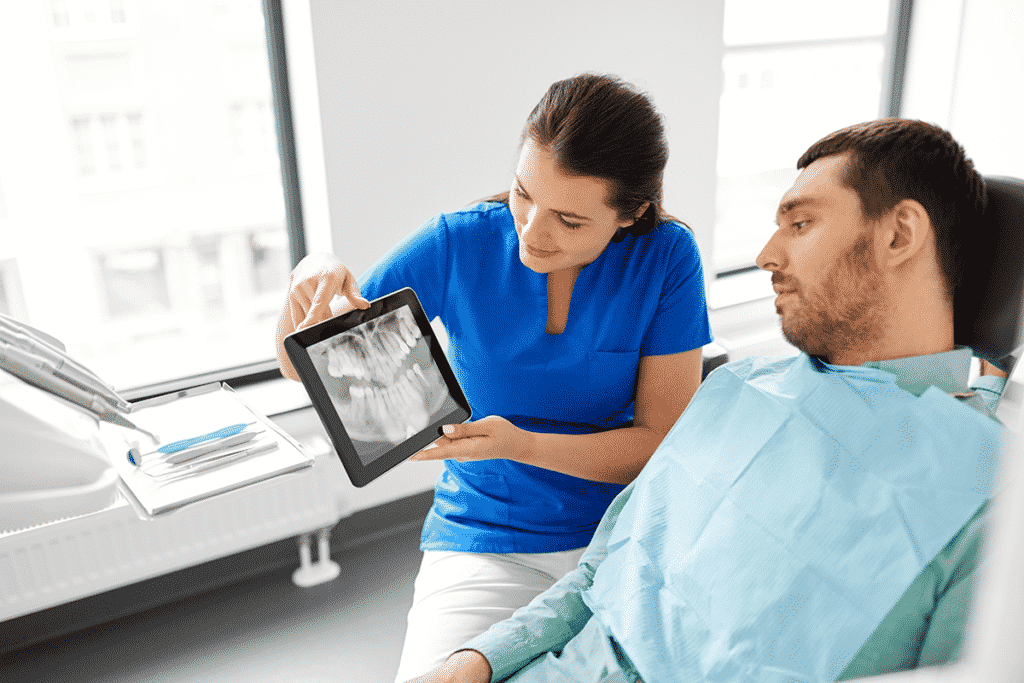 Dentist using a tablet to show patient x-rays of teeth