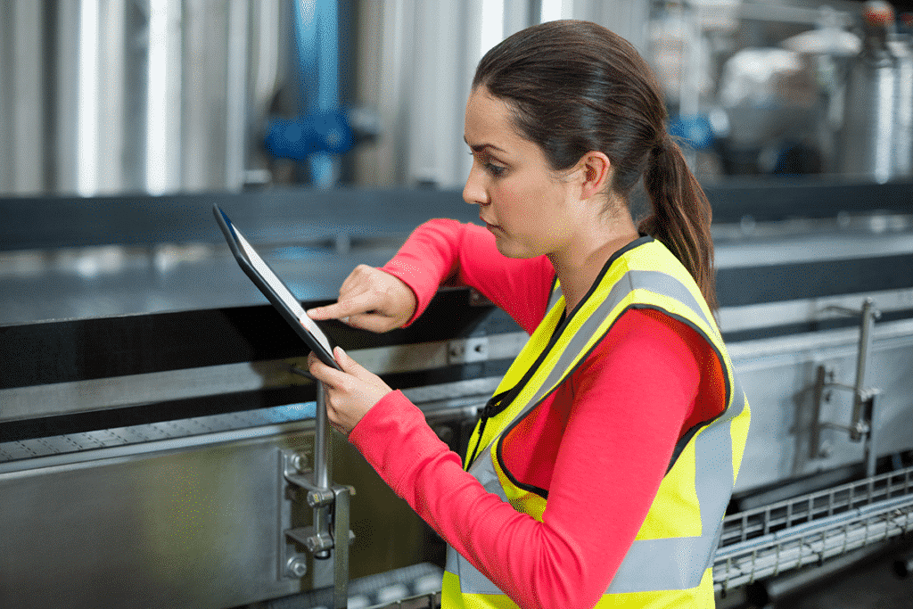 Worker reviewing data on a tablet in manufacturing environment
