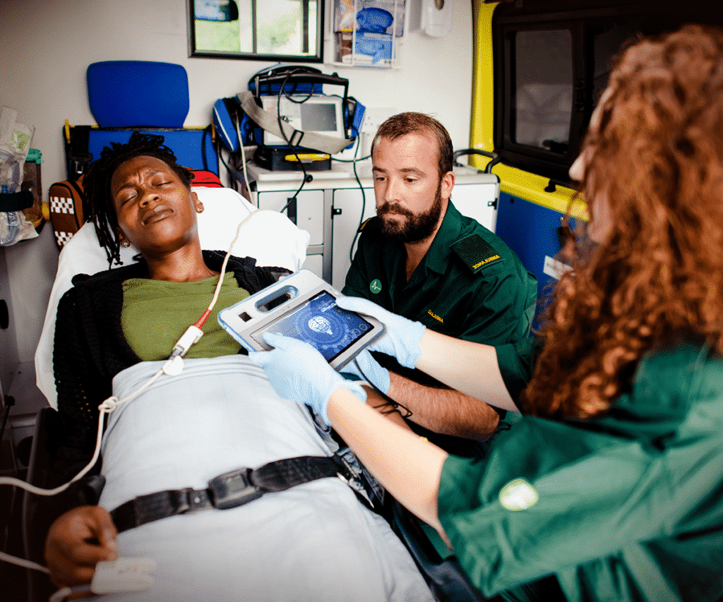 EMS personnel using the MD-100M to care for a patient in an ambulance