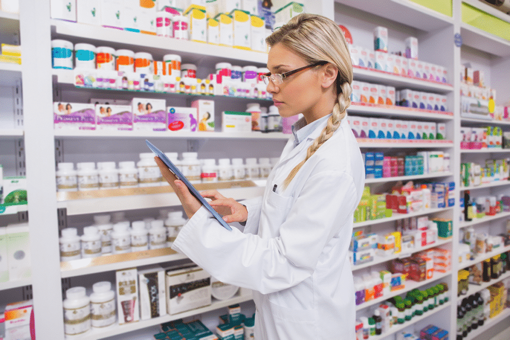 Pharmacist using a tablet to review inventory and review medical records