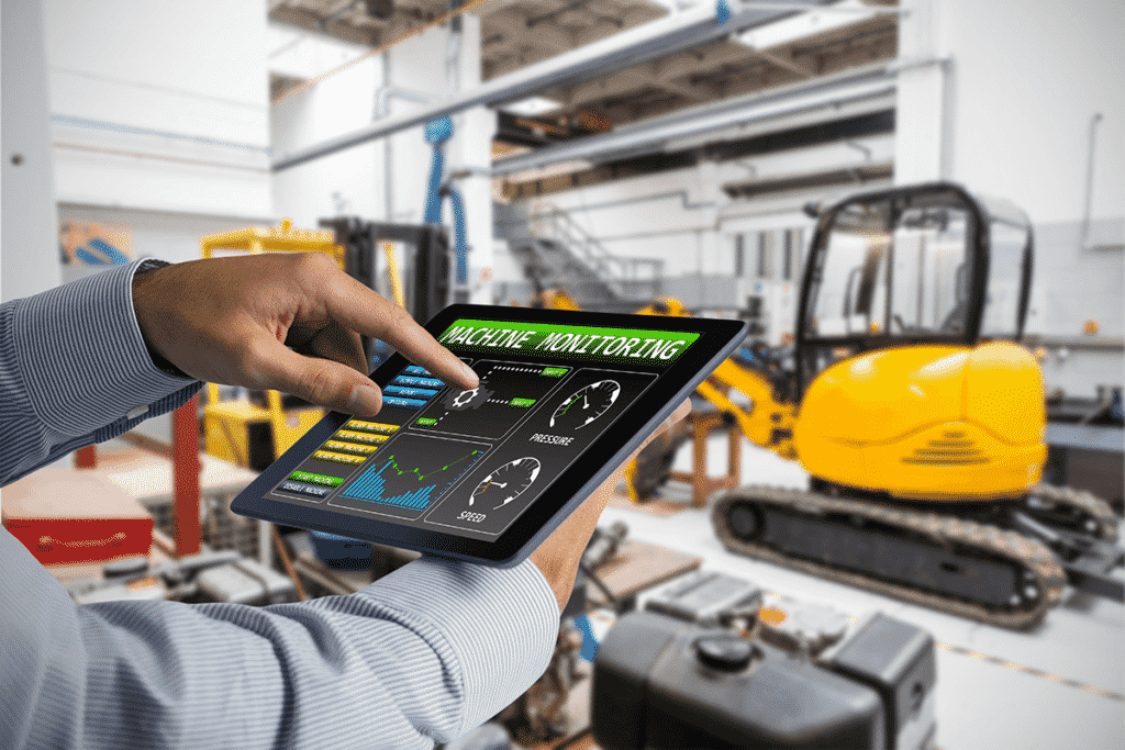 Worker using a tablet to monitor smart factory automated equipment