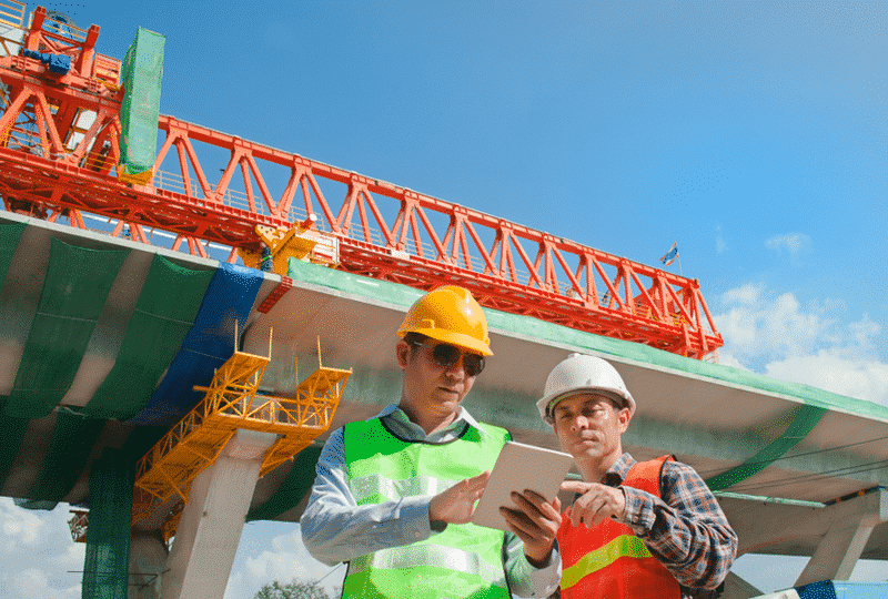 Bridge construction workers outside reading a tablet in the sunlight