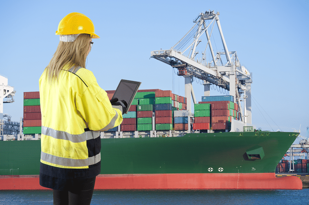 Shipping dock worker using a tablet to connect to equipment and track containers