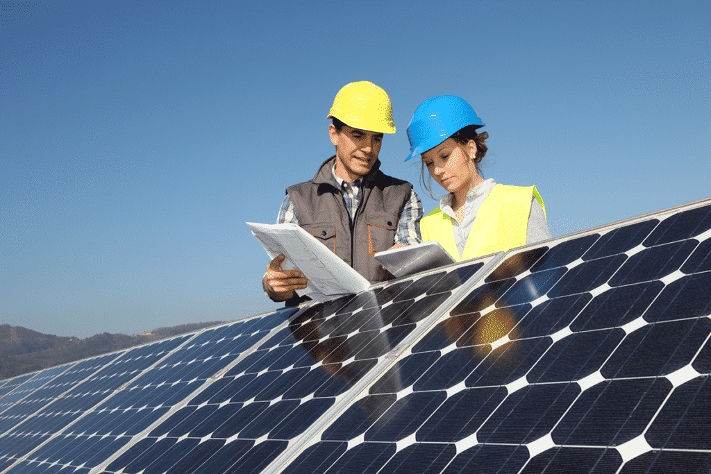 Solar energy workers using sunlight readable tablet in a solar field